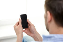Close up of man holding black smartphone at home. Business, communication, people and modern technology concept - close up of man holding black smartphone at Royalty Free Stock Photography