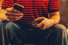 Close up of a man holding a cell phone and a tv remote control. On the other Stock Photos