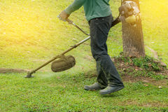 Close up of man holding grass trimmer. Royalty Free Stock Images