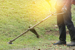 Close up of man holding grass trimmer. Royalty Free Stock Image