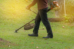 Close up of man holding grass trimmer. Royalty Free Stock Photo
