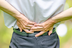 Close up of a  man holding his back in pain Royalty Free Stock Images