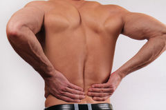 Close up of man holding his lower back. Man rubbing his painful back. . Pain relief concept Royalty Free Stock Image