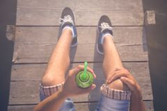 Close up of man holding kiwi juice smoothie on wooden dock. Top down viewpoint of man sitting on pier and holding glass of fresh kiwi juice with drinking straw stock photography