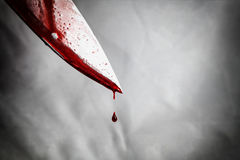 close-up of man holding knife smeared with blood and still dripp Stock Image