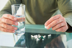 Close up of a man holding pill and glass of water Stock Image