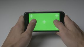 Close up man playing games with smartphone green screen chroma key on white desk background. Close up man holding smartphone touch with green screen stock video