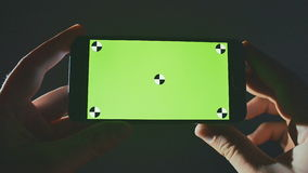 Close Up Man Holding Smartphone Touch Screen With Green Screen Chroma Key. Wathcing video.