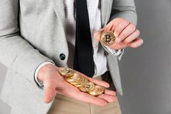 Close up of man holding stack of golden bitcoins Royalty Free Stock Photos