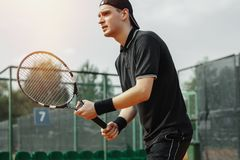 Close up of man holding tennis racket in both hands to straighten strike. Close up of young attractive man playing tennis at tennis court. Player holding outfit stock image