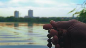 Close-up, Man Holds Rosary in His Hand, Reads Evening Prayer on the River Bank. Close-up, Man Holds Wooden Rosary in His Hand, Reads Evening Prayer on the River stock video