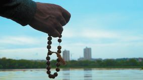 Close-up, Man Holds Wooden Rosary in Hand Standing on River Bank Producing Evening Prayer. Close-up, Man Holds Rosary in His Hand Standing on the River Bank stock footage
