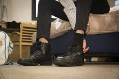 Close-up of man at home putting on shoes Stock Photo