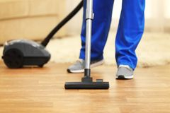 Close up of man hoovering floor with cleaner Royalty Free Stock Photo