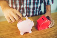 Man insert gold coin into pink piggy bank Royalty Free Stock Photography