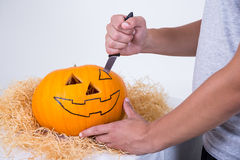 Close up of man with knife carving pumpkin Jack-O-Lantern for Ha. Lloween party Royalty Free Stock Image