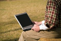 Close up man with laptop. A man sitting outside with a laptop; concept or working, shopping, or looking for a job, with copy space stock image