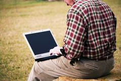 Close up man with laptop. Close up of a man with a laptop sitting outdoors typing stock photo