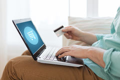 Close up of man with laptop and credit card. Technology, shopping, banking, home and lifestyle concept - close up of man with laptop computer and credit card at Royalty Free Stock Image