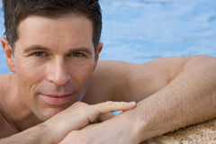 Close up of man leaning on edge of swimming pool Stock Images