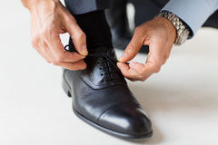 Close up of man leg and hands tying shoe laces Stock Photo