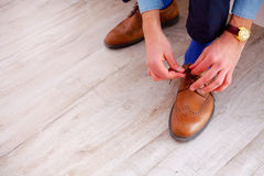 Close up of man leg and hands tying shoe laces Royalty Free Stock Image