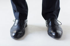 Close up of man legs in elegant shoes with laces. People, business, fashion and footwear concept - close up of man legs in elegant shoes with laces or lace boots stock photo