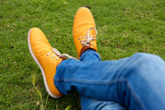 Close up man legs in jeans and shoes on green grass at park. Close up portrait of man legs in jeans and shoes on green grass at park Stock Photo