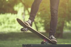 Skateboarder legs before jumping from bench in the park stock photo