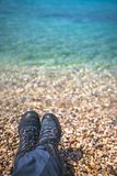Trekker feet on the stony beach. Close up of a man legs wearing black shoes resting on a stony beach in summer Stock Photos