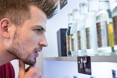 Close-up of man looking at beer bottles displayed on shelf in cafe Stock Images