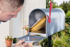 Man Opening The Mailbox. Close-up Of A Man Looking Inside The Silver Mailbox stock photography