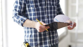 Close up of man looking and writing to clipboard stock footage
