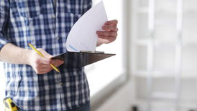 Close up of man looking and writing to clipboard