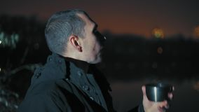 Close-up, Man Looks Away Standing on the River Bank and Drink Tea Late in the Evening stock video