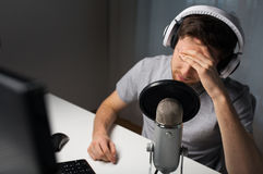 Close up of man losing computer video game. Technology, gaming, entertainment, let's play and people concept - close up of sad young man in headset with pc Stock Photos