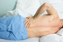 Man Suffering From A Back Pain. Close-up Of A Man Lying On Bed Suffering From A Back Pain At Home Stock Photo