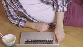 Close-up of a man lying on a wooden floor typing text on a laptop keyboard. Close-up of a man in a plaid shirt lying on a wooden floor typing text on a laptop stock footage