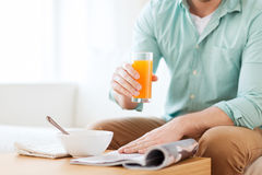 Close up of man with magazine drinking juice Stock Images
