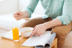 Close up of man with magazine eating breakfast Royalty Free Stock Image
