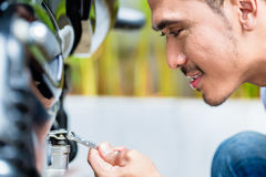 Close up of man maintaining motorcycle Stock Image
