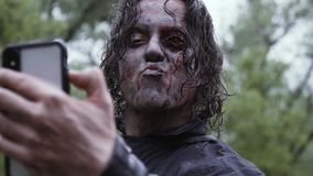 A man with zombie makeup is taking selfies and sending kisses