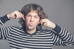 Close up of man making silly monkey face isolated on grey background. Guy grimaces monkey. Funny male holding his ears stock image