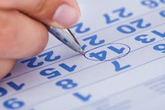 Close-up Of Man Marking On Calendar Royalty Free Stock Photo