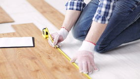 Close up of man measuring flooring and writing stock video footage