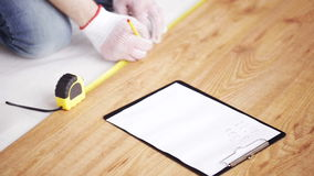 Close up of man measuring flooring and writing stock footage