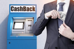 Close up of man with notes near blue atm machine Royalty Free Stock Photography