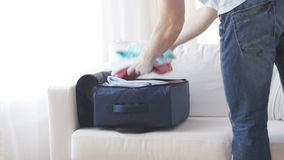 Close up of man packing clothes into travel bag. Trip, travel, vacation, luggage and people concept - close up of man packing clothes into travel bag at home stock video footage