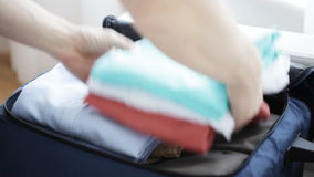 Close up of man packing clothes into travel bag. Trip, travel, vacation, luggage and people concept - close up of male hands packing clothes into travel bag at stock footage