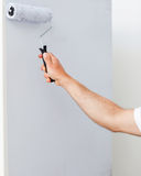 Close up of a man painting a wall in white. In his new house Royalty Free Stock Photography